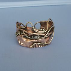 Bracelet | Cyndie Smith. Folded copper with brass wire and balls