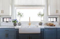 A dual farmhouse sink under a window with roman shades invites lots of light while upper cabinets showcase a swiss coffee white Benjamin Moore paint and lower cabinets display a Courtland Blue finish. LOVE this kitchen Farmhouse Kitchen Inspiration, Kitchen Decor, Kitchen Inspirations, Painting Kitchen Cabinets White, Blue Kitchens, Home Kitchens, Kitchen Design, Trendy Kitchen, Blue Kitchen Cabinets