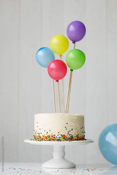 Birthday cake decorated with colorful balloons by Ruth Black for Stocksy United