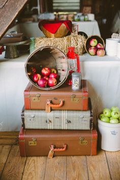 Vintage suitcases, bushel baskets, more apples, vintage kitchen supplies, vintage tin cans, lanterns, vintage scales, white pitchers, wooden crates, galvanized containers and plates, bales of hay, bunting, photos of the couple and chalkboard signs with love quotes all decorated the space.