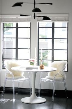Small Shop Studio - Chic breakfast nook features Saarinen Table paired with acrylic chairs accented with sheepskin pelts atop dark floors situated in front of steel and glass French windows.