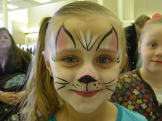 Face painting.  Cat or Kitten.  Put a light wash of white, then pink on the ears and nose, then use a thin liner with the black.  Adorable.