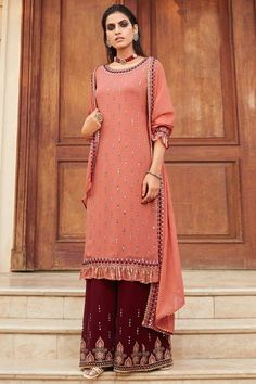 Specifically designed for a stylish lady like you is this peach georgette sharara suit which will give a very sassy look. This round neck and 3/4th sleeve party wear attire beautified with mirror and thread work. Paired with georgette sharara pant in maroon color with peach georgette dupatta. Sharara pant has mirror and thread work. #shararasuits #malaysia #Indianwear #weddingwear #andaazfashion Sharara Suit, Salwar Kameez, Salwar Suits, Indian Attire, Indian Ethnic Wear, Wedding Wear, Wedding Suits, Pantalon Cigarette, Pakistani Suits Online