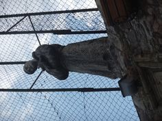 Saints are everywhere in Assisi, Italy, but this one looks like he's fenced in!