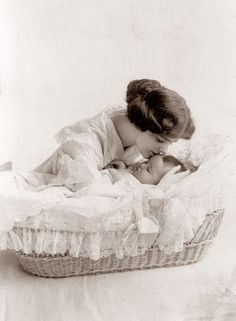 Mother gently kisses her baby as she sleeps peacefully in her basinet. 1912