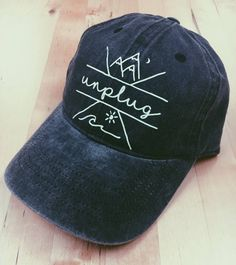 The hat reads unplug inside a hand drawn design with mountains and ocean waves in a criss cross logo size. This baseball cap is charcoal with white vinyl. The hat is complete with an adjustable strap in the back. All products on my shop are designed by me so you won't be seeing them anywhere