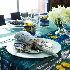 Gelt, foil-wrapped chocolate coins, inspired this table for Hanukkah. Wrap napkins with bead-and-coin-festooned ribbon, use a scarf as a table runner, and dress up simple plastic boxes of gelt with ribbon./