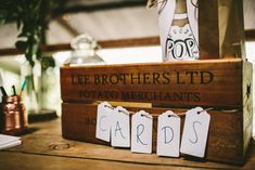 Image by Samuel Docker Photography - Claire Pettibone lace dress in a rustic barn wedding in the Cotswolds with red bridesmaid dresses. Groom wears a Reiss Suit with floral bow tie and light up letters decoration.
