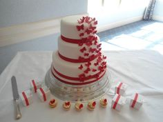 large 3 tier wedding cake in white icing with red satin ribbon and a flurry of red sparkly butterflies cascading up the side of the cake. Matching mini cupcakes were made as favours for the wedding guests