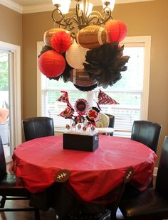 Suspended superbowl decoration. We love that football paper lantern and how they decorated this party. Red, white paper lanterns, accordion lantern & black tissue paper pom pom combined with football paper lantern