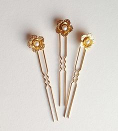 Hair pins are an easy way to add a subtle touch of elegance to a formal hairdo. For those brides that don't want accessories to get too complicated, these pins work wonders. They're fashioned from brass flowers and freshwater pearls.