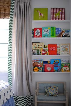 Cute idea for book wall. It would keep them from throwing all the books out of the bookcase to find the one they want!