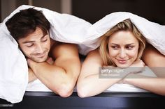 Romantic young couple lying under bedsheet in bed with arms crossed