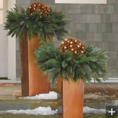 Column Planter We could spray paint wood, gold to make a planter and then make a less holiday looking arrangement with greens, branches and twinkle lights.