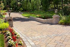 Beautiful entryway includes custom stone driveway