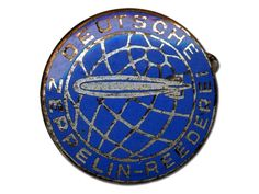 Hindenburg uniform service badge, 1936-37 (#5)    Navigator Max Zabel's uniform bore the rank insignia for Hindenburg third officers. Worn low on the sleeve, the branch of service badge showed the globe in blue enamel with a silver airship. He wore one gold sleeve stripe (which would have been on the shoulder boards for his white jacket), and a thin gold cord interwoven with black adorned his hat.