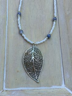 Bohemian style long white beaded necklace with angelite and big silver colored leaf shaped pendant.