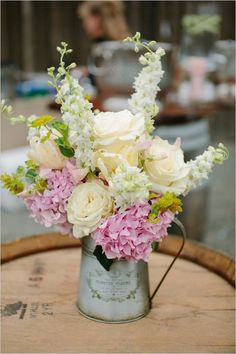 Adorable arrangement in a watering can, with Larkspur, Garden Roses, and Hydrangea // The Wedding Chicks