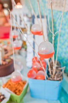 """camping party: plastic bubble containers--like in toy vending machines--filled with gummy worms as """"bobbers and bait"""", tied on stick fishing poles  {Fresh Chick Design Studio}"""