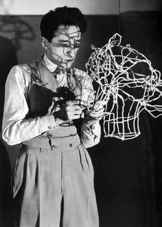 Jean Cocteau sculpting his head in wire,  photographed by Man Ray circa 1925.