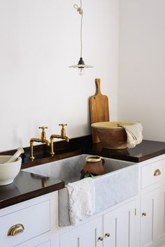 Glossy hardwood worktops work perfectly withe the marble sinks, a lovely rich contrast and a timeless look