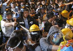 Battle: Photos show hundreds of police battling with demonstrators on the streets of Hong Kong