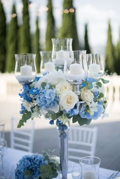 Silver Candelabrum with Pale Blue Hydrangeas and White Roses for Elegant Wedding Tablesetting<br> The Tuscan Wedding Planners is highly skilled and knowledgeable in their field. In fact, they are experts with many years of experience and training. Blue Wedding Decorations, Blue Wedding Centerpieces, Quinceanera Centerpieces, Blue Wedding Flowers, Wedding Flower Arrangements, Floral Wedding, Blue Hydrangea Centerpieces, Blue Hydrangea Bouquet, Pastel Blue Wedding