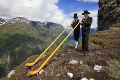These men are  blowing in a wind instrument on a place called Nebbet in the valley Nærøydalen in Sogn county.