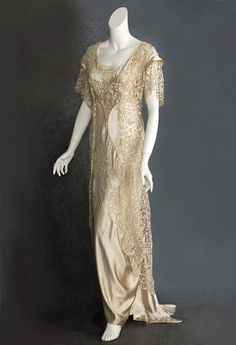 Beaded satin/lace wedding dress, c.1912. The long lean lines and empire waist are in the Directoire style; while the elaborate beading, draped lace, hobbled asymmetric skirt, and fishtail train are early 20th century innovations. Loops of sparkling crystal beads complete the inspired ornamentation.