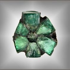 """Trapiche emeralds are in a class by themselves and are perhaps the rarest and most memorable of """"pattern"""" gems—certainly the most unusual amongst the big three of emerald, ruby, and sapphire. Trapiche is the Spanish word for a spoked wheel used to grind sugar cane, which bears a striking resemblance to the pattern in these emeralds. Normally they are cut en cabochon to display the beautiful spoke-like star."""
