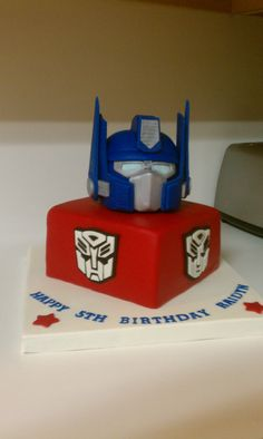 Optimus Prime Transformer cake - Optimus is rkt covered in a fondant/gumpaste mixture. Funny story...I was drying the side pieces in the oven and Hubby preheated the oven for pizza. I got a very apologetic text. It's okay though, the second set turned out better than the first.