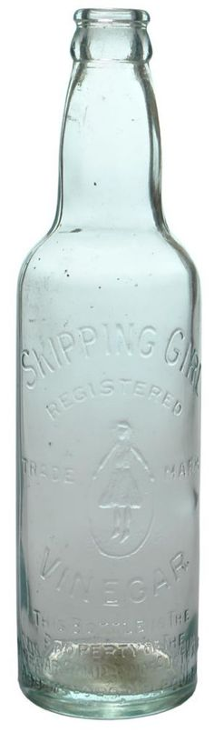 """Skipping Girl Vinegar. The property of the Vinegar Company of Australia, Abbotsford, Melbourne (Victoria). Little Audrey trade mark. Clear glass (very faint aqua). Crown seal. Seam through lip. 13 oz. """"Modern"""" AGM base mark. c1940s. Very unusual in this colour. ABCR Auction 11, Lot 616. Excellent condition. Hammer Price: $135."""