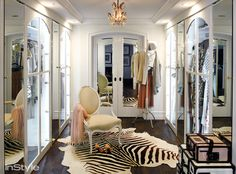 Lauren Conrad - Glamorous closet features small crystal chandelier illuminating an oval back French chair atop black and white zebra cowhide rug layered atop oak floors placed in front of bi-fold mirrored closet doors flanked by arched glass closets intermixed with mirrored closets.