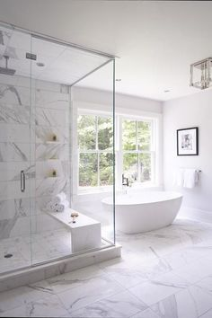 An oval freestanding bathtub paired with a modern polished nickel tub filler is positioned on white marble floor tiles beneath a window and beside a seamless glass shower.