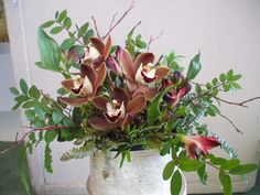 Brown mini cymbidium orchids in a twiggy arrangement with a bleached birch container, highlighted with red alstro. Designed at A Flower Shop on Okanagan Avenue.
