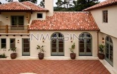 Exterior of a SPANISH STYLE LUXURY HOME with stucco walls a red tile roof and MEXICAN TILE PATIO photo