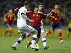 Spain's Fernando Torres fights for the ball with Italy's Giorgio Chiellini and Riccardo Montolivo during their Confederations Cup semi-final soccer match at the Estadio Castelao in Fortaleza