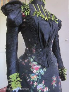 Dress from the Belle Epoque, circa 1895-1900.  The fabric is a rich ottoman brocaded silk with garlands of flowers in the Louis XV french taste manner. This high quality silk probably belongs to a prestigious European manufacture (Lyon? Spittafield?). The sleeves are covered with black silk bubbled gauze, the bodice is decorated with jet beads and ruffles of black and green silk ribbons.