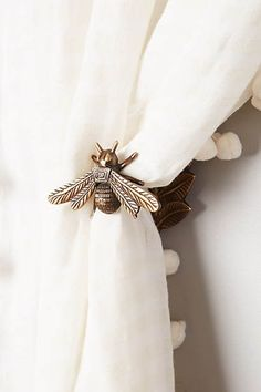 This is why I LOVE Pinterest ....I saw this, loved it, went straight to my jewelry box and pulled out earrings I have that are just like these bees. Put on my own curtains in my guest bedroom and voila.....swy
