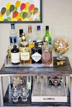 A gentleman's bar cart. Brandy sniffer with collection of corks, lucite box housing all liquor, lucite box hosing all glasses.