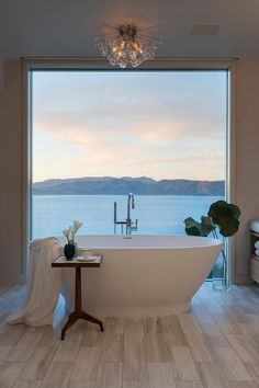 Water front home boasts a restful bathroom featuring a floor to ceiling picture window positioned behind an oval freestanding bathtub matched with a polished nickel gooseneck deck mount tub filler illuminated by a sputnik flush mount light.
