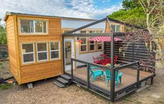 A 28' tiny house on wheels. This side entrance model includes a living room, large galley kitchen with upper cabinets on one side, and two loft bedrooms.