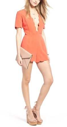 A plunging neckline puts a daring twist on this coral romper styled with scalloped trim and leg-flaunting shorts.