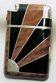 """American Art Deco cigarette case/lighter. Circa 1935. Slide-A-Light by Marathon. Black and tortoise shell enamel on chrome. Sunburst motif. With original velvet lined presentation case, carrying pouch, manufacturer's instructions in cellophane wrapper, cleaning brush. Approximate dimensions: 4 1/4"""" x 2 1/2"""". Near mint condition. Minor surface scratches."""
