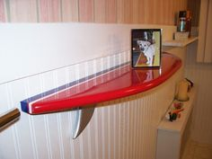 Red Surfboard Wall Shelf With Framed Photo Of Dog On It