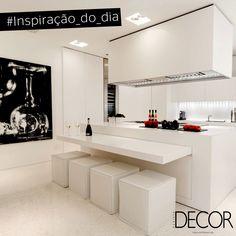 Toda em branco, a cozinha conta com uma bancada integrada à mesa e quatro assentos que se assemelham a pufes. O moderno quadro garante o contraste com os mobiliários, adornos e revestimentos e se destaca no ambiente. Elegante e funcional, o espaço apresenta estilo contemporâneo.