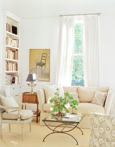 A compact, but comfy living room. Love the neutral palette and white drapes...
