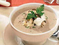 Für die Cremige Champignon-Suppe Zwiebel schälen und fein würfeln. Champignons putzen und in Scheiben schneiden. Petersilie waschen, trocken
