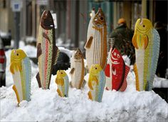 Painted fish sculptures on display in snowbank outside a shop on Gloucester's Main St.