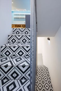 A narrow staircase with rectangular black-and-white patterned tiles and a tall white metal banister leads down to the basement photography studio.
